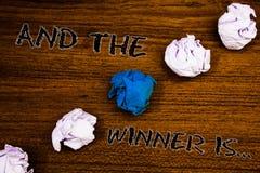 El texto de la escritura de la palabra y el ganador es El concepto del negocio para anunciar como primero coloca en la mesa arbol fotos de archivo libres de regalías