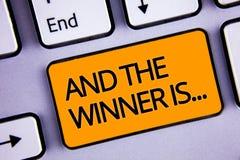 El texto de la escritura de la palabra y el ganador es El concepto del negocio para anunciar como primero coloca en yello platead fotografía de archivo