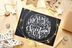 El texto de la Feliz Navidad en una pizarra con los deoccrusties de la Navidad protagoniza, guirnalda en fondo de madera Fotograf Foto de archivo libre de regalías