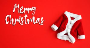 El texto de la Feliz Navidad y capa de Santa Claus Saint Nicholas la mini se adaptan al fondo rojo vivo aislado la endecha blanca fotografía de archivo