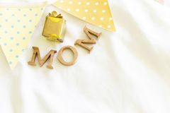 El texto de madera de la mamá con la caja de regalo y la bandera del partido de la tela en la tela blanca texturizan el fondo Imagen de archivo