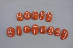 El texto del feliz cumpleaños con la naranja pintó piedras sobre la arena blanca fotos de archivo