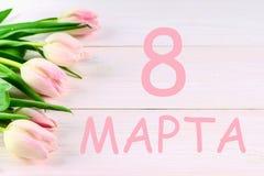 El texto en ruso: a partir del 8 de marzo Día internacional del ` s de las mujeres Tulipanes en una tabla de madera blanca Imagen de archivo libre de regalías
