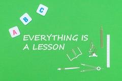 El texto everyting es una lección, desde arriba de fuentes de escuela de madera de los minitures y de letras del ABC en fondo ver Foto de archivo