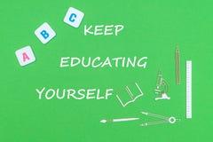 El texto guarda el educarse, desde arriba de fuentes de escuela de madera de los minitures y de letras del ABC en fondo verde Imagen de archivo libre de regalías