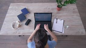 El texto que mecanograf?a del estudiante en el teclado del ordenador port?til y escribe notas en el tablero que se sienta en el e almacen de video