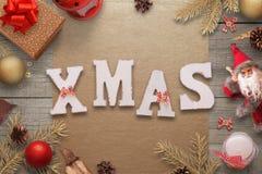 El texto rodeado con las decoraciones de la Navidad, abeto de Navidad ramifica, muñeca de Papá Noel, regalos, linterna, bolas Foto de archivo