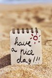 El texto tiene un día agradable en una libreta en la playa Imagen de archivo