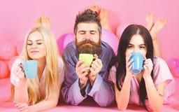 El Threesome se relaja por mañana con café Concepto de los amantes Hombre y mujeres, amigos en la endecha soñolienta de las caras fotos de archivo