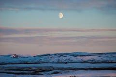El tiempo crepuscular en la Islandia rural con la luna grande apareció en el fondo fotografía de archivo