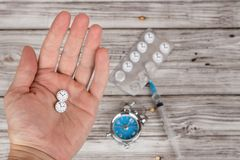 El tiempo cura concepto Mano masculina que sostiene píldoras estilizadas como reloj Alarma y medicina imagen de archivo libre de regalías