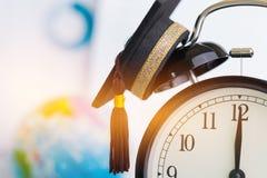 El tiempo es la educación, casquillo de la graduación en el concepto superior del reloj de educat imagenes de archivo