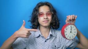 El tiempo es oro el adolescente divertido en vidrios rosados sostiene un reloj en sus manos y muestra a sus fingeres la muestra d almacen de metraje de vídeo
