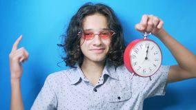 El tiempo es oro el adolescente divertido en vidrios rosados sostiene un reloj en sus manos y muestra a sus fingeres la muestra d almacen de video