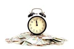 El tiempo es oro concepto con cierre para arriba de un reloj viejo en billetes de dólar Imagen de archivo libre de regalías