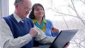 El tiempo libre de las compras en línea, los pares mayores con el ordenador se sientan en Internet y sonríen almacen de metraje de vídeo