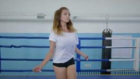 El tiempo libre, la muchacha joven del atleta entrena con una cuerda en el ring de boxeo en estudio de los deportes almacen de metraje de vídeo