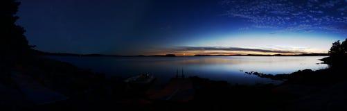 El tiempo traslapa panorama: El lago con una puesta del sol a la derecha y la noche protagonizan el cielo a la izquierda imagen de archivo