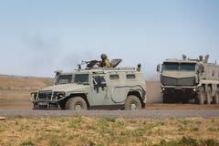 El tigre multiusos del vehículo blindado GAZ-233014 y Kamaz-63968 se están moviendo en un terreno de entrenamiento militar fotos de archivo