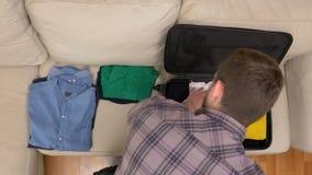 El timelapse de la visión superior del embalaje del hombre viste en la maleta almacen de metraje de vídeo