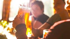 El tintinear con los amigos que usan el vidrio de cerveza Imagenes de archivo