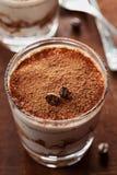 El Tiramisu en vidrio en la tabla del vintage, café tradicional condimentó el postre italiano Imágenes de archivo libres de regalías