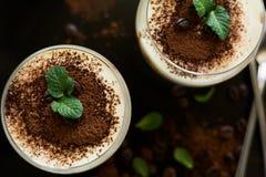 El tiramisu italiano tradicional del postre adornó el cacao, los granos de café y las hojas de menta Fotografía de archivo