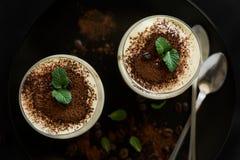 El tiramisu italiano tradicional del postre adornó el cacao, los granos de café y las hojas de menta Foto de archivo