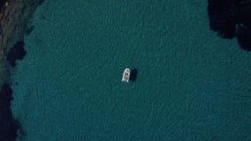 El tiro aéreo de los pares felices que se relajaban y que tomaban el sol en un barco parqueó en el medio del agua mediterránea má almacen de metraje de vídeo