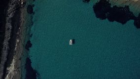 El tiro aéreo de los pares felices que se relajaban y que tomaban el sol en un barco parqueó en el medio del agua mediterránea má almacen de video