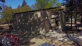 El tiro aéreo del solo edificio del cocrete en el emplazamiento de la obra en la cámara del bosque vuela hacia la casa y el edifi metrajes