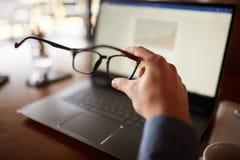 El tiro aislado primer de sirve la mano que sostiene las lentes delante de la pantalla del ordenador portátil con las cartas y lo imagen de archivo