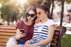 El tiro al aire libre de dos hembras adolescentes hermosas mira atento en el teléfono elegante, leyó la información en Internet,  Fotografía de archivo