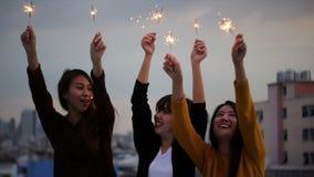 El tiro al aire libre de la gente joven en el tejado va de fiesta El grupo feliz de amigas de Asia goza y juega de la bengala en  metrajes