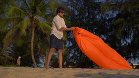 El tiro a cámara lenta de un hombre joven infla un sofá inflable en una playa hermosa almacen de metraje de vídeo