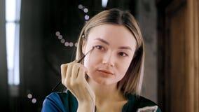 El tiro cercano de la aplicaci?n multi-?tnica joven hermosa atractiva de la mujer blanca compone por la ma?ana cerca del espejo e metrajes