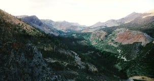 El tiro cinemático aéreo del bosque hermoso cubrió la montaña, el canto rocoso masivo y el camino en el parque nacional de Yosemi metrajes