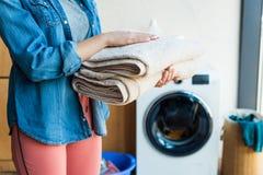 el tiro cosechado de la tenencia de la mujer joven apiló las toallas limpias en casa imagen de archivo libre de regalías