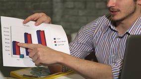 El tiro cosechado de una demostración del hombre de negocios imprimió diagramas en una reunión de negocios almacen de metraje de vídeo