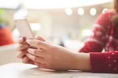El tiro cosechado del modelo femenino irreconocible en suéter rojo utiliza el teléfono celular moderno para la comunicación en lí fotografía de archivo libre de regalías