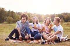 El tiro de adolescentes felices ríe alegre mientras que tenga comida campestre al aire libre, bebida que la energía fría bebe, si Foto de archivo