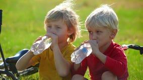 El tiro de la cámara lenta de dos cyclers de los niños pequeños se sienta en un agua del césped y de la bebida del las botellas p almacen de metraje de vídeo