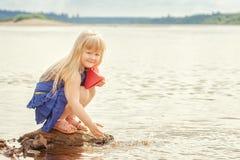 El tiro de la feliz muchacha quiere funcionar con el barco de papel en el lago Imágenes de archivo libres de regalías