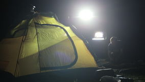 El tiro de la noche de dos sirve la erección de la tienda en ligh de SUV expedicionario almacen de metraje de vídeo