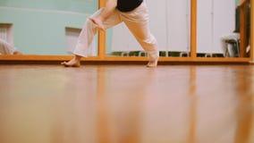 El tiro de piernas del combatiente masculino realiza trucos marciales con los elementos de la danza en el entrenamiento del capoe almacen de video