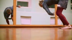 El tiro de piernas del combatiente masculino realiza trucos marciales con los elementos de la danza en el gimnasio del deporte de almacen de video