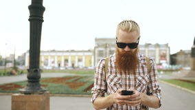 El tiro de Steadicam del hombre turístico barbudo con la calle que camina de la mochila y el smartphone con para la visión trazan almacen de video