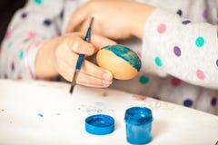 El tiro del cepillo de la tenencia de la muchacha y el éster de la pintura egg Imagen de archivo