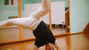 El tiro del combatiente masculino realiza trucos marciales con los elementos de la danza delante del espejo almacen de video