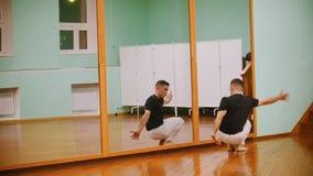 El tiro del combatiente masculino realiza trucos marciales con los elementos de la danza en el entrenamiento del capoeira delante metrajes